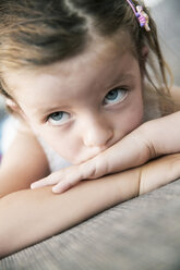 Sad looking little girl lying on sofa, close-up - JATF000396