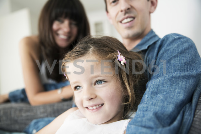 Young parents with little daughter sitting on sofa at home - JATF000398 - Jan Tepass/Westend61