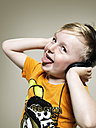 Portrait of little boy, showing his tongue while listening music, studio shot - STKF000378