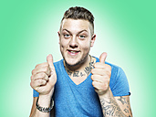 Portrait of happy young man with thumps up, studio shot - STKF000387