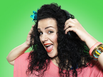 Portrait of young woman hearing music with headphones, studio shot - STKF000393