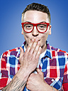 Portrait of ashamed young man wearing red glasses, studio shot - STKF000399