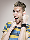Portrait of enthusiastic young man clenching his fists, studio shot - STKF000411