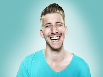Portrait of laughing young man, studio shot - STKF000413