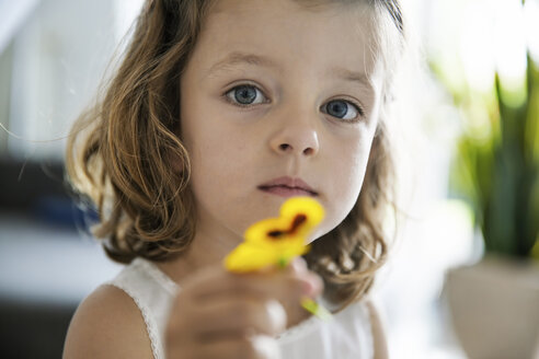 Little girl holding pansy blossom in her hand, close-up - JATF000408