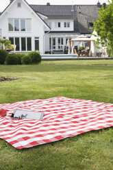 Germany, Cologne, Tablet pc on blanket in garden - PDF000554