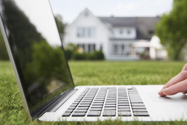 Germany, Cologne, Man using laptop in garden - PDF000555