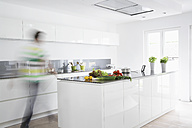 Germany, Cologne, Man in kitchen, blurred motion - PDF000560