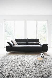 Germany, Cologne, Football and chips in front of couch - PDF000540