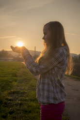 Germany, Weiden, teenage girl holding the sun in her hands - SAR000117