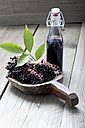 Elderberries (Sambucus), leaves on a wooden shovel and a bottle of elderberry juice on white wooden table, studio shot - CSF020262
