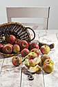 Organic apples (Malus), basket and a knife on white wooden table, studio shot - CSF020299