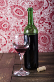 Red wine and red wine glass on wooden table - ODF000582
