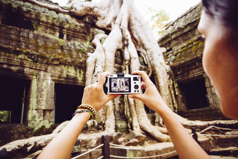 Cambodia, Angkor Wat, Woman takes pictures of the famous tree in Ta Prohm Temple - MBEF000767
