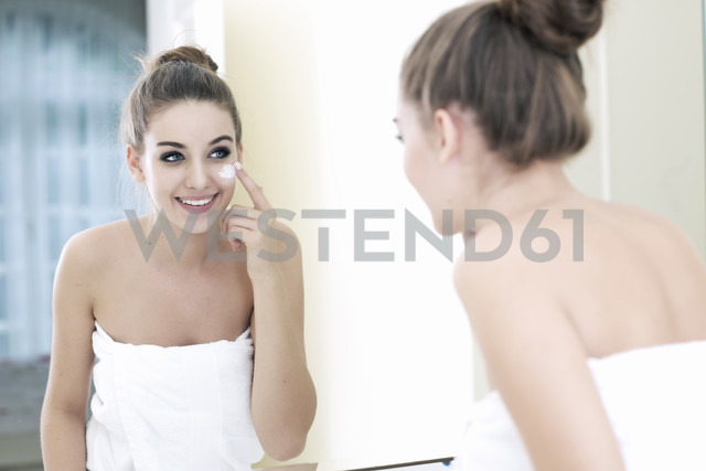 Portrait of teenage girl putting on some lotion while looking at her mirror image - GDF000254 - Gabi Dilly/Westend61