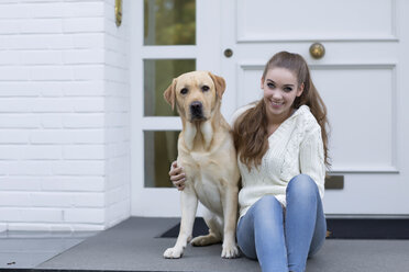Teenage girl with dog sitting in front of an entry door - GDF000285