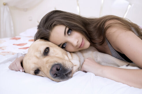 Portrait of teenage girl lying on bed with her dog - GDF000287
