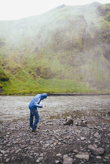 Iceland, Tourist at Skogafoss Waterfall - MBEF000764