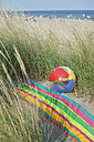 Italy, Adriatic, beach ball and towel on sand dune with grass - CRF002505