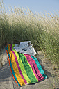 Italy, Adriatic, newspaper, sunglasses and towel on sand dune with grass - CRF002506