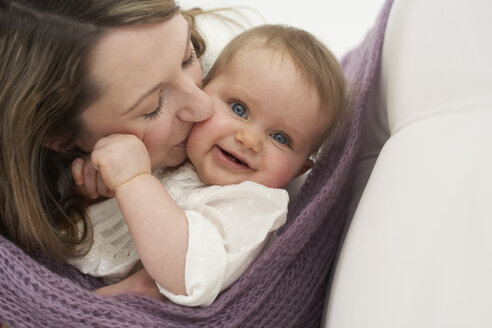 Mother kissing her smiling baby girl - FSF000025