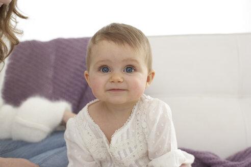 Portrait of smiling baby girl sitting on sofa - FSF000033