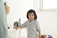 Asian woman photographing her little daughter with smartphone - FSF000087