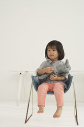 Little Asian girl with soft toy sitting on a chair - FSF000068