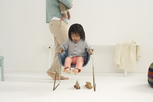 Little Asian girl sitting on a chair, mother and sister at the background - FSF000095