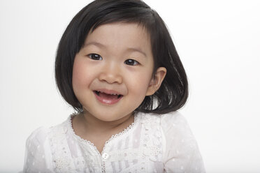Portrait of little Asian girl smiling, studio shot - FSF000080