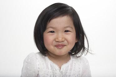 Portrait of little Asian girl smiling, studio shot - FSF000082