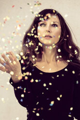 Young woman looking at confetti in the air - NGF000048