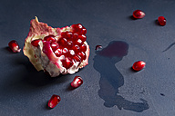 Pits and piece of pomegranate [Punica granatum] on blue wood, close-up - MYF000059