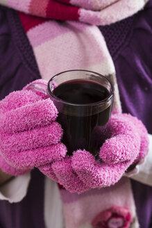 Hands of little girl holding glass of hot fruit tea - STB000113
