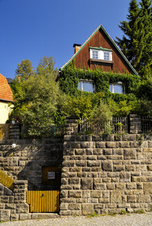 Germany, Saxony, Hohnstein, Overgrown house behind stone wall - BT000227