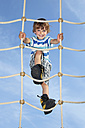 Portrait of smiling little boy standing on climbing net - RDF001223
