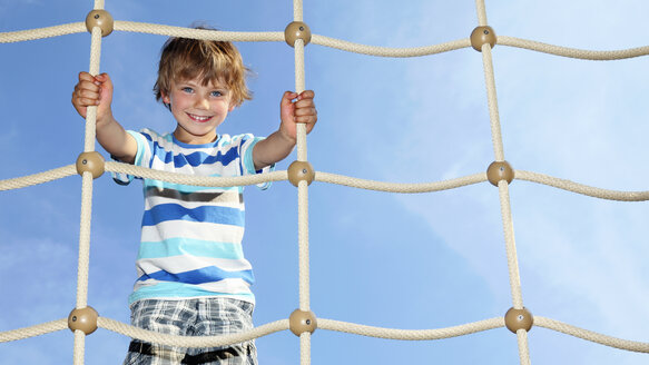 Portrait of smiling little boy standing on climbing net - RDF001224