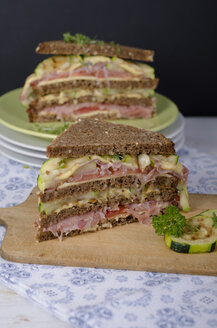 Whole-grain bread sandwiches with ham, roasted zucchinis, tomatoes and cheese on plate and on chopping board garnished with cress, studio shot - ODF000625