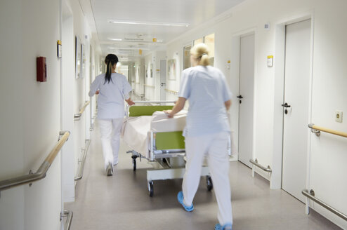 Germany, Freiburg, Nurses moving hospital bed - DHL000136
