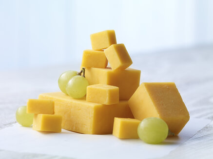 Stack of diced cheddar cheese with green grapes on wooden table - SRSF000324
