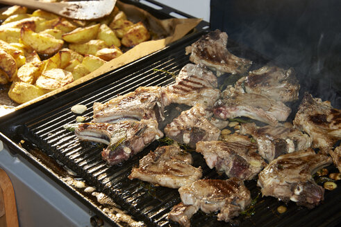 Marinated lamb chops on barbecue grill and potatoe wedges - SRSF000318