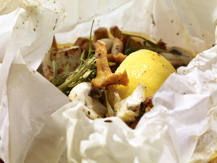 Mushrooms, potato dumpling and rosmary in parchment paper, close-up - SRSF000301