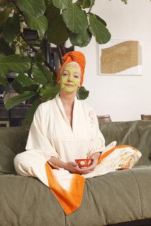Germany, Dusseldorf, Senior woman with face mask sitting on sofa - UKF000255