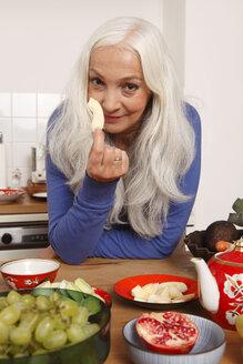 Germany, Dusseldorf, Senior woman eating raw food - UKF000222