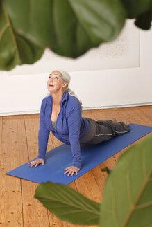 Germany, Dusseldorf, Senior woman practicing yoga - UKF000224