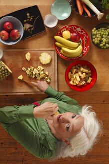 Germany, Dusseldorf, Senior woman preparing raw food - UKF000226
