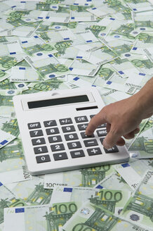 Man pressing calculator key on 100 euro notes - ASF005222