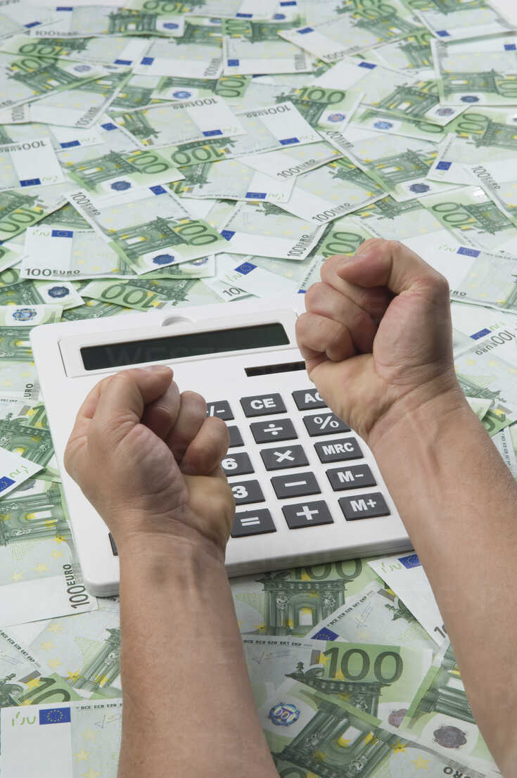 Man making fist over calculator on 100 euro notes - ASF005221 - Achim Sass/Westend61
