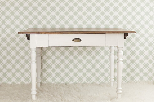 Old kitchen table in front of ornamental wallpaper, studio shot - DRF000270