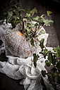 Halloween decoration, glittering pumpkin with ivy tendril on wooden table - SBDF000332